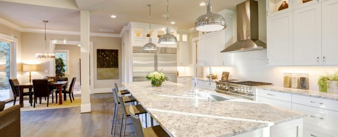 White kitchen design features large bar style kitchen island with granite countertop illuminated by modern pendant lights. Northwest USA