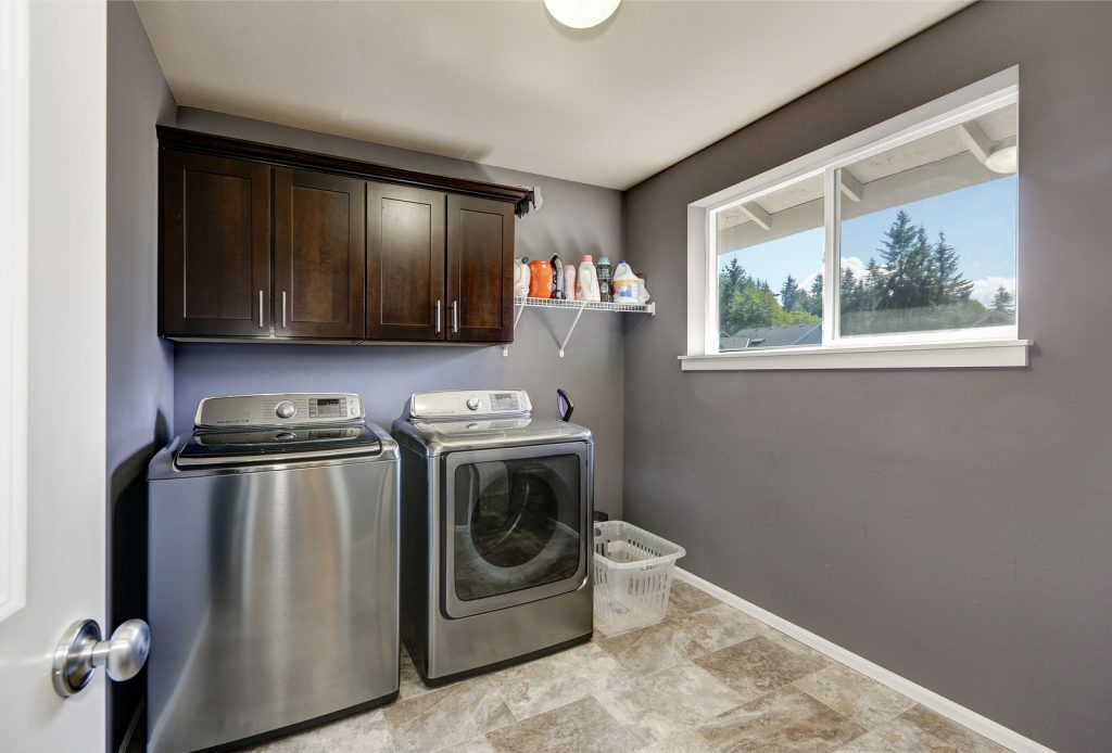 Grey laundry room with modern stainless steel washing machine and dryer brown cabinets and tile floor. Northwest USA