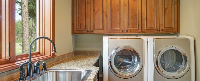Huge laundry room with white washer and dryer, brown wood cabinets, granite countertop framing the sink with black faucet. Northwest, USA