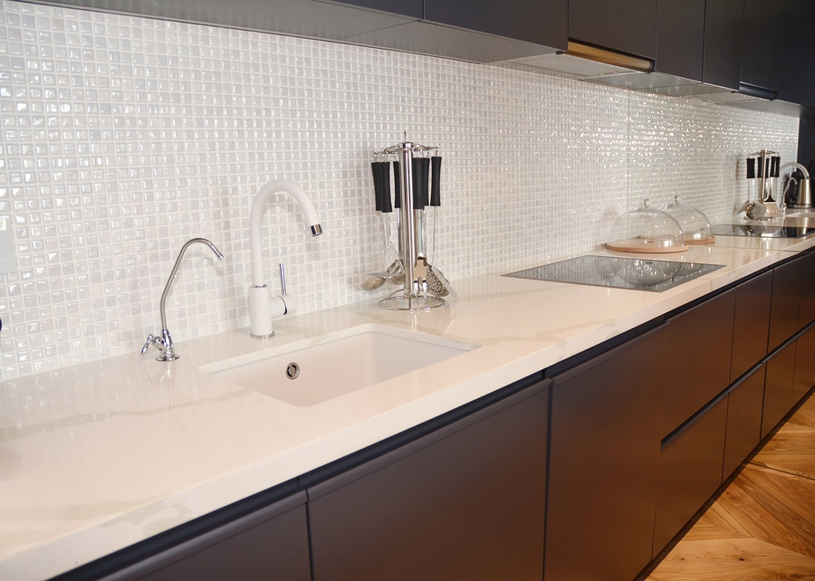 Modern kitchen metal faucet, cooker hood and ceramic kitchen sink. Ceramic kitchen sink with kitchen table.