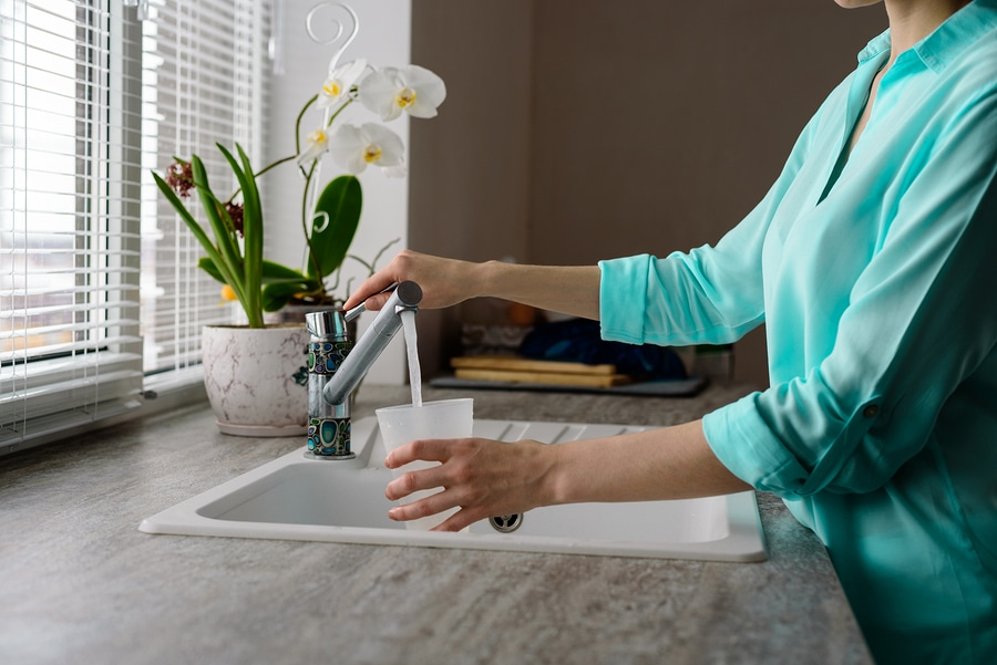 close-up of a woman collects water in a plastic glass from the tap in the kitchen sink in front of the window.