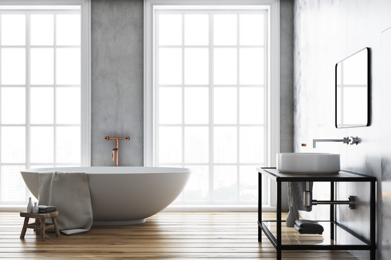 Luxury bathroom interior idea. A wooden floor, a large window and a white bathtub and sink. Concrete walls. 3d rendering mock up