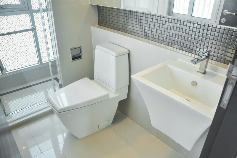 Nicely decorated modern bathroom with toilet and sink.